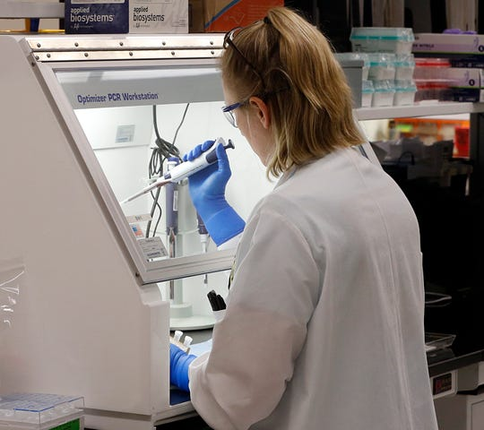 An employee of the Department of General Services Division of Consolidated Laboratories' Virginia Public Health Labratory adds chemicals in the second step of testing a sample for the Coronavirus at the lab in Richmond, Va. on Wednesday, March 4, 2020.