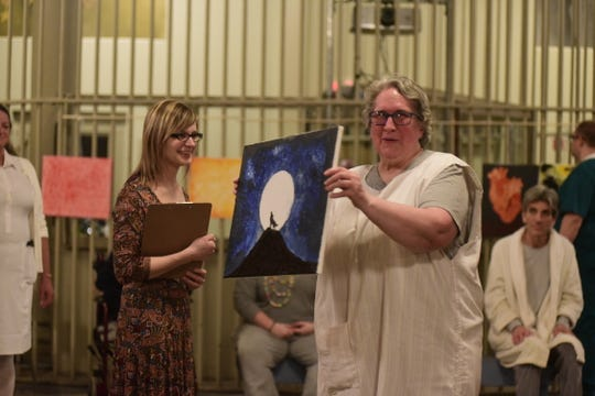 Ginny, played by Suzanne Allen, shows off a painting she made while living inside the insane asylum.