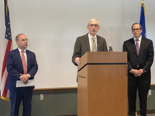 Gov. Tony Evers is flanked by Transportation Secretary Craig Thompson, left, and Brown County Executive Troy Streckenbach, right, during an announcement of $75 million in new road funding made in Suamico in Brown County on Wednesday, March 4, 2020.