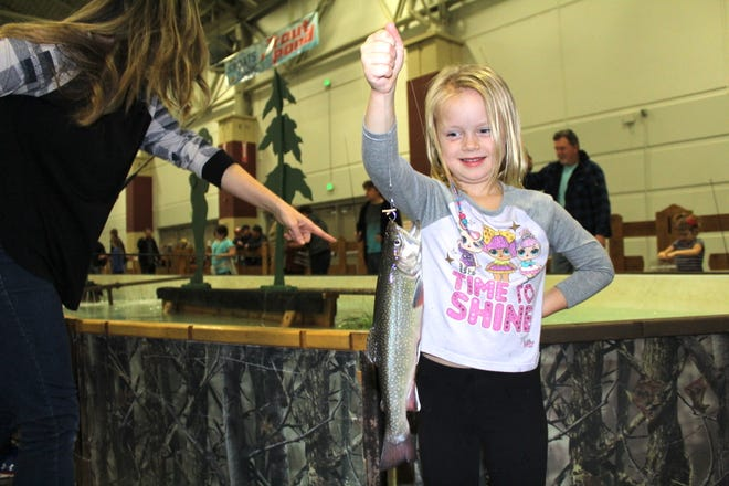 Abby Heritsch, 6, of Oconomowoc holds a brook trout she caught Wednesday while fishing with her family at the trout pond at the Milwaukee Journal Sentinel Sports Show.