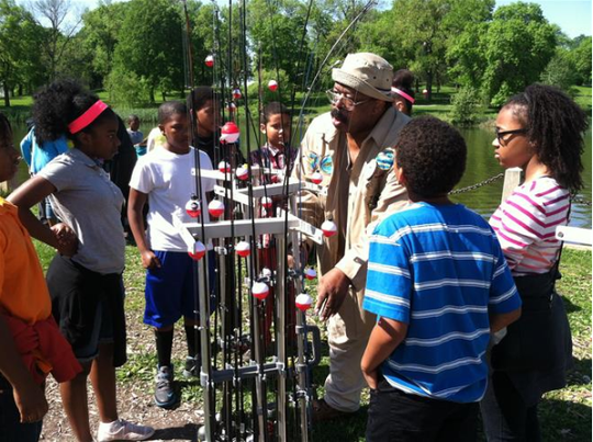 E.B. Garner, center, teaches students from Mount Calvary Lutheran School how to safely use a fishing pole during a recent visit to the Washington Park lagoon in 2014.