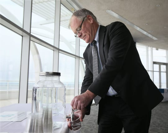Waukesha Mayor Shawn Reilly fills a cup with Milwaukee water before a ceremony in 2017 announcing a partnership between Waukesha and Milwaukee to provide Waukesha with a new water supply.