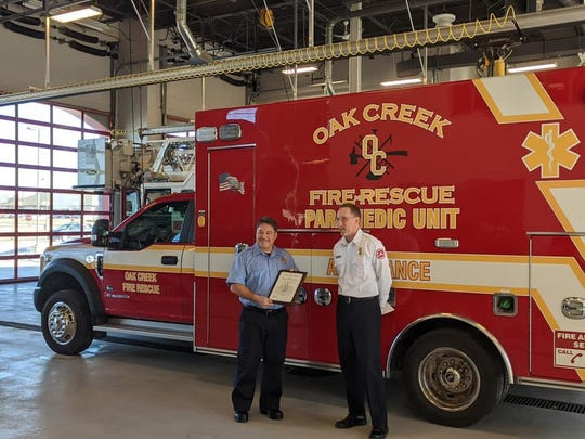Michael Wargolet (left), a firefighter with the Oak Creek Fire Department, was recognized Feb. 28 by Chief Mike Kressuk (right) for his off-duty actions in saving an infant in Illinois Feb. 17.