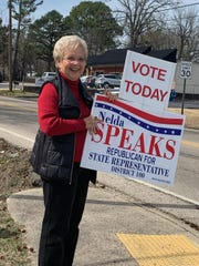 District 100 State Rep. Nelda Speaks holds up a campaign sign in front of the Eastside Baptist Church voting center on Tuesday.