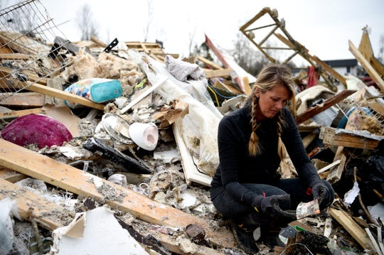 On Wednesday, March 4, 2020, Roslyn Wear sorts through the debris of a home where a family died in Tuesday's tornado in Cookeville, Tenn.