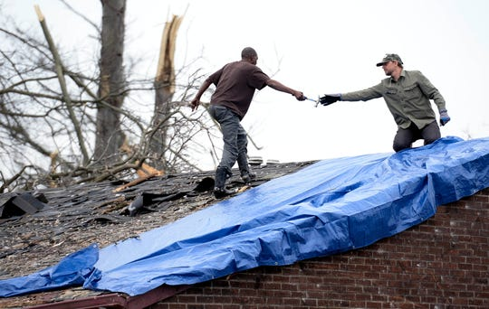 Two men work together nailing down a tarp on a tornado-damaged home along Underwood Street on Wednesday, March 4, 2020, in North Nashville, Tenn.