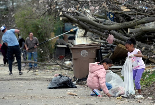 Maysa, 8, and Mora Hawkins, 6, pick up trash and debris around tornado-damaged homes on Monroe Street in North Nashville on Wednesday, March 4, 2020.