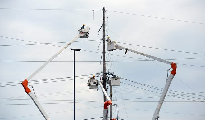 Nashville Electric Services repair tornado-damaged power lines Monroe Street on Wednesday, March 4, 2020, in North Nashville, Tenn.