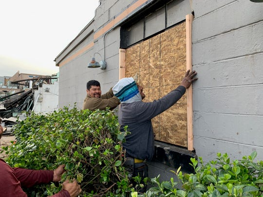 Workers from AccuWorks restoration company board up a window at Drifters Tennessee Bar-B-Que Joint in East Nashville. The owners of the bar and restoration company know each other through Entrepreneurs' Organization (EO Nashville)