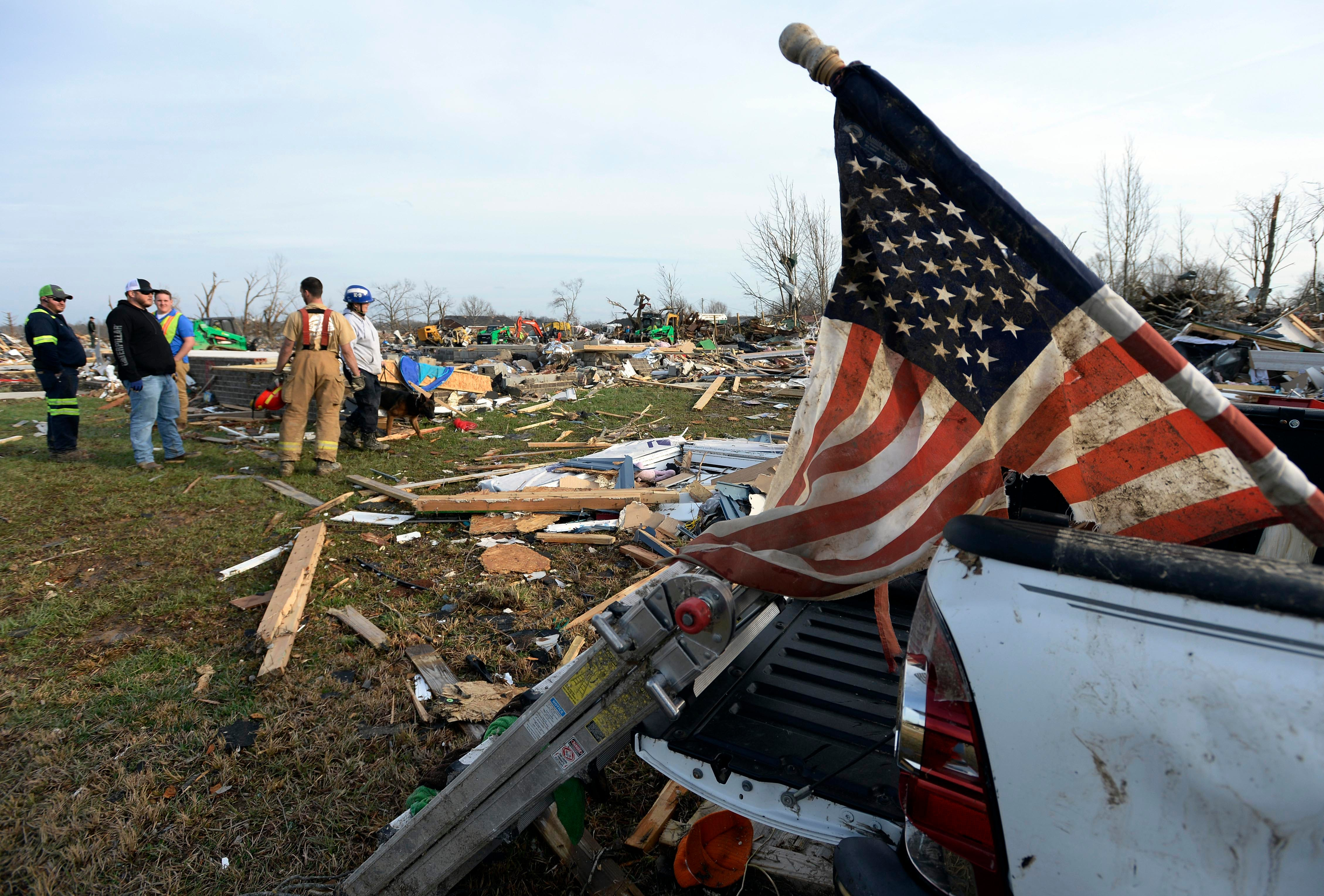 A search-and-rescue dog team from Ohio and Tennessee Task Force Recovery, left,  head out to look for missing people in debris near Hensley Street after a tornado destroyed homes on Tuesday, March 3, 2020, in Cookeville, Tenn.