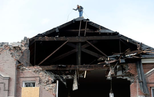 Artemio Salgado puts rope across the top of the tornado damaged Hopewell Baptist Church before covering the opening with a tarp on Wednesday in North Nashville.