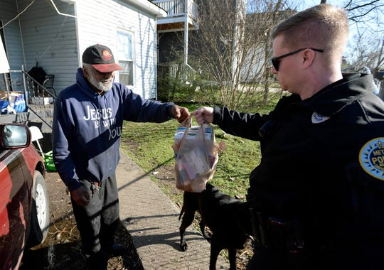 Mosses Berry, 76, receives a bag of food from Metro Nashville Police Department officer Ryan Burger at his home on Understood Street on Wednesday.