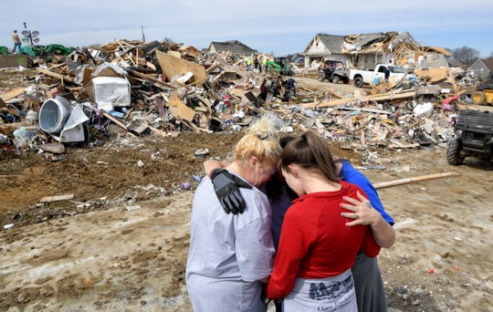 Donna Barnett and daughter Jessica Garrett are hugged and given a prayer by Lindsey Holloway and Melody Montgomery Wednesday, March 4, 2020, in Cookeville, Tenn.,  after a tornado touched down earlier in the week.