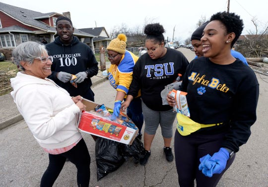Tennessee State University students take a quick break from cleaning up along tornado-damaged homes on Underwood Street on Wednesday, March 4, 2020, in North Nashville, Tenn.