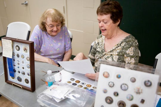 """Carol Hilberg, right, talks about the buttons she's purchased at auctions with Lynn Dodson, left, during a Gulf Breeze Button Club meeting at Golden Gate Community Center on Tuesday, March 3, 2020. """"I've never met a button I didn't like,"""" Hilberg said."""