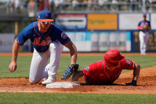 Washington Nationals' Andrew Stevenson, right, dives safely back to first ahead of the tag from New York Mets first baseman Pete Alonso during the second inning of a spring training baseball game Sunday, March 1, 2020, in Port St. Lucie, Fla.