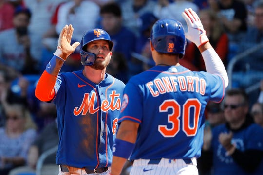 New York Mets' Jeff McNeil (6) is congratulated by teammate Michael Conforto (30) after scoring on a two-run double by Robinson Cano during the first inning of a spring training baseball game against the Washington Nationals Sunday, March 1, 2020, in Port St. Lucie, Fla.