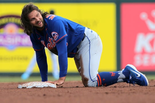 Mar 1, 2020; Jupiter, Florida, USA; New York Mets center fielder Jake Marisnick (16) reacts after being tagged out in the fourth inning of the game against the Miami Marlins at Roger Dean Chevrolet Stadium.