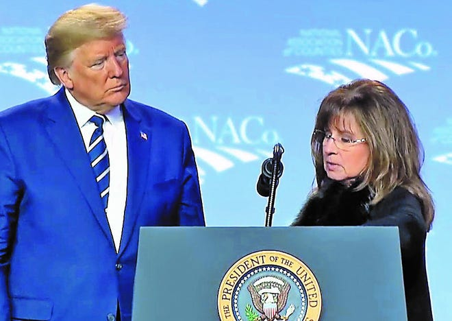 U.S. President Donald Trump pauses in a speech to the National Association of Counties in Washington, D.C., Tuesday to invite Lea County Commission Chairwoman Rebecca Long to talk about the oil boom in southeastern New Mexico. Long credited the Trump administration for reducing permit times and increasing oilfield jobs since his presidency began in 2017.