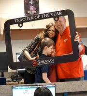 Novi Educational Foundation Teacher of the Year Brad Miller is congratulated by his family during a March 4, 2020 celebration at Novi Middle School. From left are his wife Amy and children Luke, 10, and Nicholas, 8.