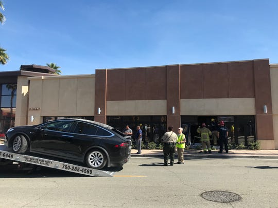 A Tesla is removed after its driver crashed into Mastro's Steakhouse on El Paseo in Palm Desert Wednesday, March 4, 2020. Cal Fire reported its driver was not injured.