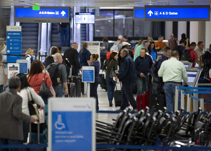 Travelers check in with American Airlines at Phoenix Sky Harbor International Airport Terminal 4 on March 4, 2020.