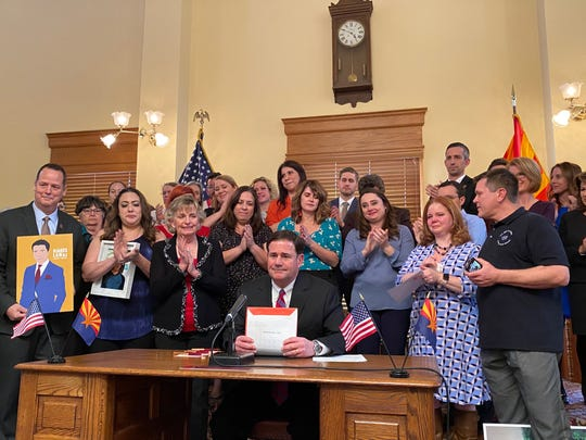 Gov. Doug Ducey (center) signs Jake's Law at the state Capitol on Tuesday, March 3, 2020. The wide-ranging mental health bill passed unanimously in the House and Senate.