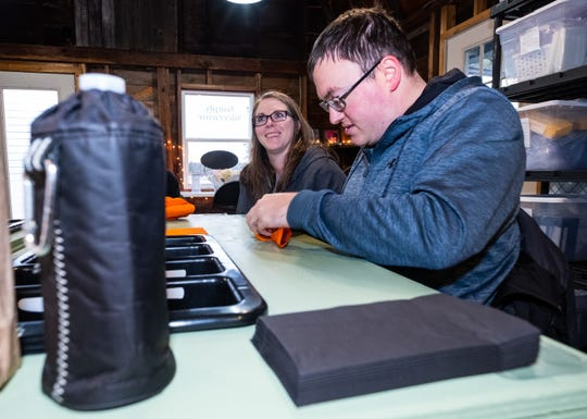 Jenn Gildenpfennig, owner of Simply Silverware, left, works with Patrick Myers Tuesday, March 3, 2020, at her business' new location in St. Clair.