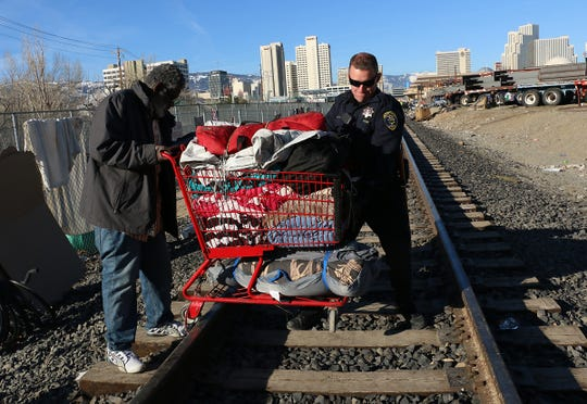 RPD Officer Gott helps Stephen Frazier get over the tracks with his belonging while being evicted from a homeless encampment in Reno on March 4, 2020.