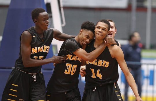 McQuaid's Jermaine Taggart (14) is congratulated by teammates Kobe Long and Rueben Daniel after his three free throws in the final seconds helped the Knights beat Victor 61-60 in the Class AA semifinal.
