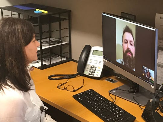 """Colette Madison, a physician assistant with Rochester Regional Health, demonstrates a telehealth connection. The """"patient"""" is RRH employee Cole Nardi."""