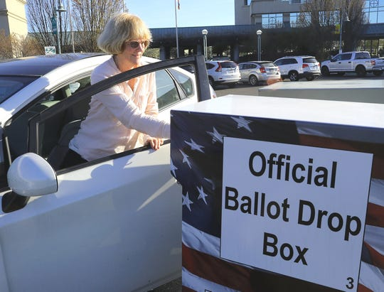 Judy Champagne puts her mail-in ballot in the drop box outside Redding City Hall on Tuesday, March 3, 2020, for the presidential primary election.