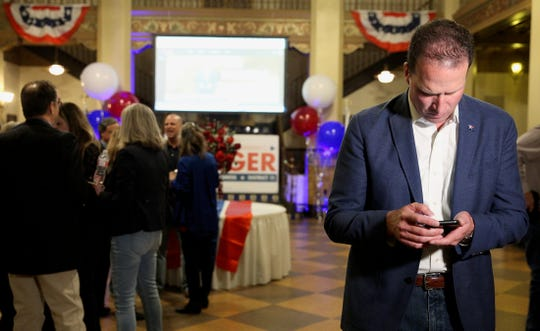 August Pfluger, right, keeps an eye on his phone at an election night watch party at the Cactus Hotel as results come in Tuesday, March 3, 2020.