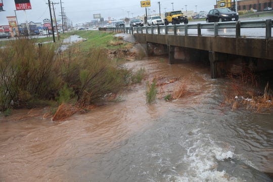 The Red Arroyo behind Enterprise Rent-A-Car swells at the Sherwood Way crossing during heavy rain Wednesday, March 4, 2020.