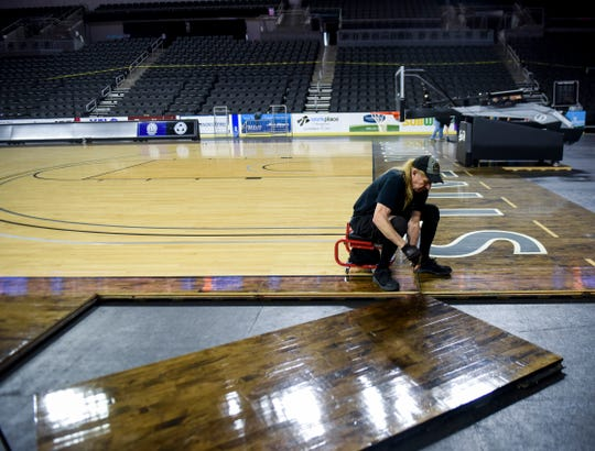 Crews install the basketball court in preparation for the Summit League tournament on Wednesday, March 4, 2020 at the Denny Sanford Premier Center.