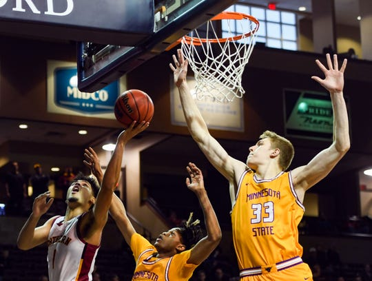 Northern State University's Tommy Chatman makes a layup as Minnesota State University's Corvon Seales and Kelby Kramer jump to block the shot during the Northern Sun Intercollegiate Conference championship game on Tuesday, March 3, at the Sanford Pentagon in Sioux Falls.