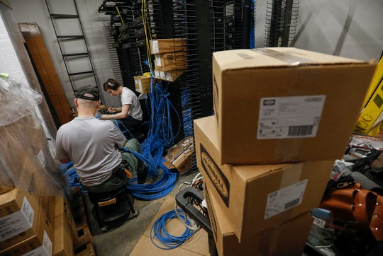 Information technology employees work to run cable at the Ozarks Technical Community College's new center in Republic on Wednesday, March, 4, 2020.