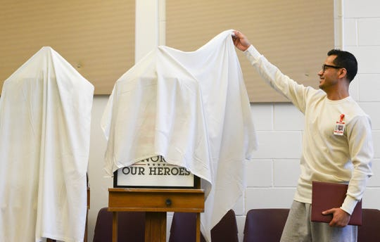 Sergio Zapata lifts off the sheet hiding his artwork honoring the fallen soldiers Wednesday, Mar. 4, 2020, at the St. Cloud prison.