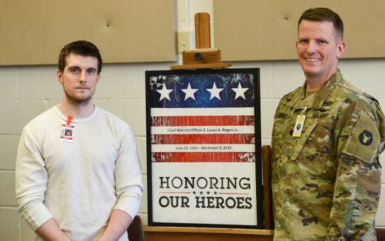 Jason Ricci and Jeremy Degeier pose for a photo with the painting honoring Chief Warrant Officer 2 James A. Rogers Jr. Wednesday, March 4, 2020, at the St. Cloud prison.