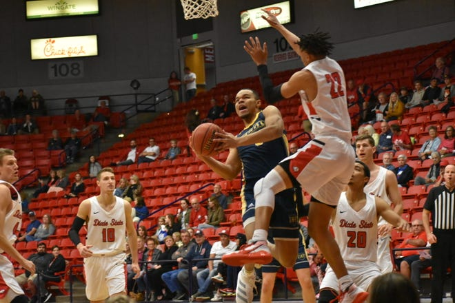 Regis' Brian Dawson drives against Dixie State's Frank Staine (22) in the RMAC Quarterfinals at Burns Arena.