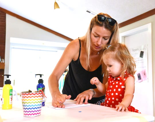 Paulina Sutter helps her daughter Isobel paint a butterfly using a piece of yarn at Yellow Bobby Pins Art Camp.