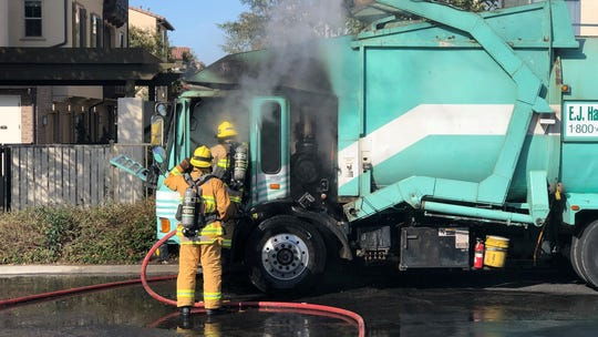 Crews work to put out the fire in a garbage truck on West Daily Drive in Camarillo on March 4, 2020.