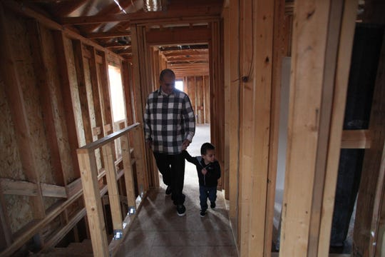 Roberto Castro and son Aaron walk through their new Habitat for Humanity home in Camarillo.
