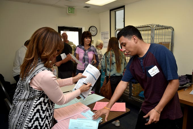Jorge Hernandez, 19, registers to vote in his first election at the Conejo Valley Unified School District headquarters in Thousand Oaks with help from elections official Naomi McCoy on Tuesday.
