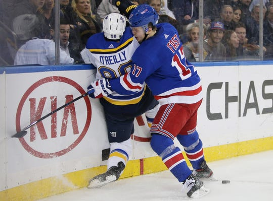 Mar 3, 2020; New York, New York, USA;  New York Rangers right wing Jesper Fast (17) checks St. Louis Blues center Ryan O'Reilly (90) during the second period at Madison Square Garden.