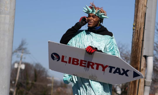 20-year-old Imeer Dorsey adjust his music between dancie moves in the parking lot of Liberty Tax Service where he spins a sign dressed as Lady Liberty promoting the seasonal tax business.