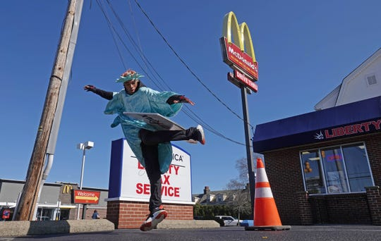 20-year-old Imeer Dorsey kicks a promotional sign in the air while dancing in the parking lot of Liberty Tax Service dressed as Lady Liberty promoting the tax business on the corner of Philadelphia Pike and Harvey Rd.
