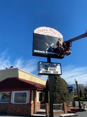 A new sign for TenderBones Rib Shack goes up at the former location of Where Pigs Fly in Dover on Wednesday afternoon.
