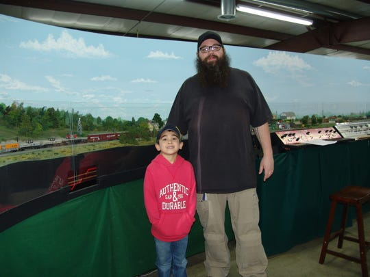 Club member Lance Hall poses with his son Samson in front of a section of model train at the club's building at the fairgrounds.