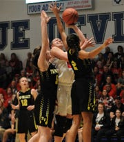 Sheridan's Faith Stinson puts up a shot over Tri-Valley's Lexi Howe (2) and and Janie McLoughlin (5) in the Division II regional semifinal on Tuesday at Zanesville. The Scotties won 50-48.